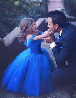 Фото Девочка в пышном синем платье трогает отца