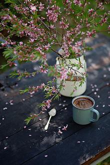 Фото Кружка кофе на столе и бидончик с весенней веткой на столе