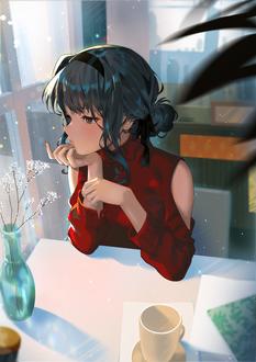 Фото Девушка сидит за столом, на котором стоит чашка и ваза с цветами