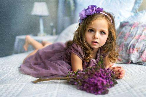 Фото Красивая зеленоглазая девочка с ободком в волосах лежит на постели, рядом с ней цветы