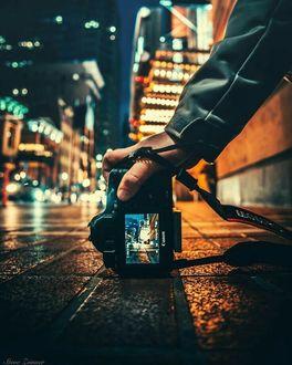 Фото В руке мужчины фотоаппарат, который он держит на асфальте на фоне ночного города
