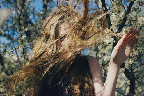 Фото Девушка с длинными волосами стоит у цветущих весенних веток дерева