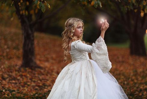 Фото Девочка в белом платье с магией над рукой, ву Katie Andelman