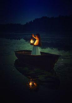 Фото Девочка с горящим фонарем стоит в лодке