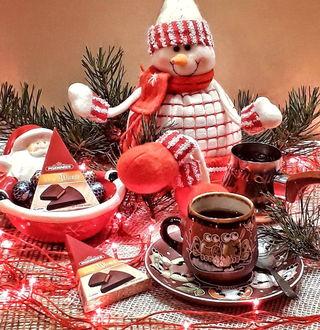 Фото Фигурка снеговика, турка с чашечкой кофе на блюдце, ваза с конфетами среди хвои на столе