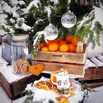 Фото На улице под елкой, украшенной шарами, прямо на снегу стоит ящик с мандаринами и разные предметы