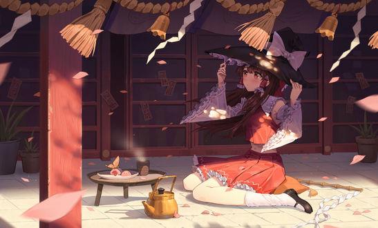 Фото Девочка в шляпе сидит перед столиком и чайником