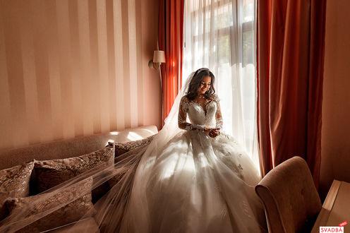 Фото Девушка в свадебном наряде стоит в комнате
