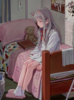 Фото Девочка сидит на кровати рядом с игрушечным мишкой, сидящим у подушки