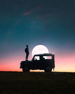 Фото Парень с рюкзаком за спиной стоит на капоте машины на фоне ночного неба полной луны, by Gokul Raj