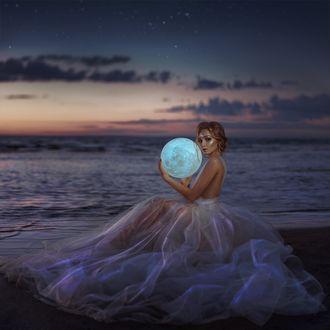 Фото Модель Татьяна Новичкова держит в руках шар в виде луны на фоне моря. Фотограф Александра Литвинова