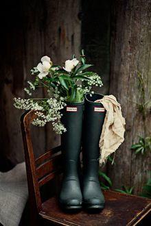 Фото Цветы и тряпка в резиновых сапогах, которые стоят на стуле