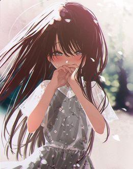 Фото Девочка с длинными волосами держит руки у лица