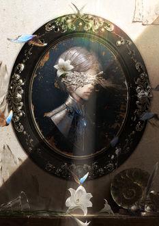 Фото Женский портрет, с повреждением в области глаз, в рамке, висящий на стене