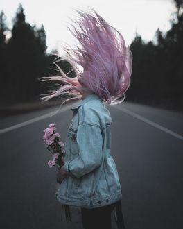 Фото Девушка с розовыми волосами в джинсовой куртке стоит на дороге, держа в руках цветы, by Ashley Brehm