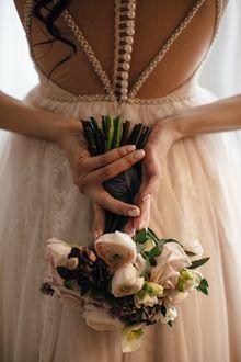 Фото В руках невесты, стоящей к нам спиной, букет цветов
