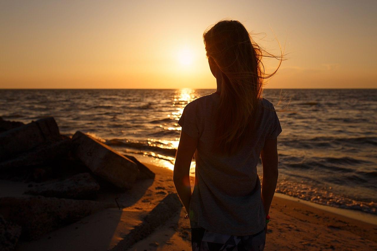 Фото Девушка стоит на фоне заката солнца над морем. Фотограф Сергей Невзоров