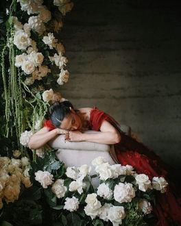Фото Девушка в красном платье сидит на кресле в комнате с цветами