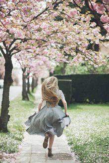 Фото Девушка с длинными волосами бежит по дорожке с цветущими весенними деревьями
