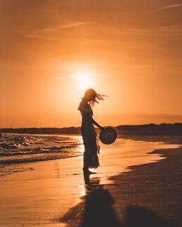 Фото Девушка со шляпой в руке стоит на фоне заката, by matt. ferr
