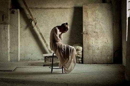 Фото Девушка грустит, сидя на стуле в пустой комнате