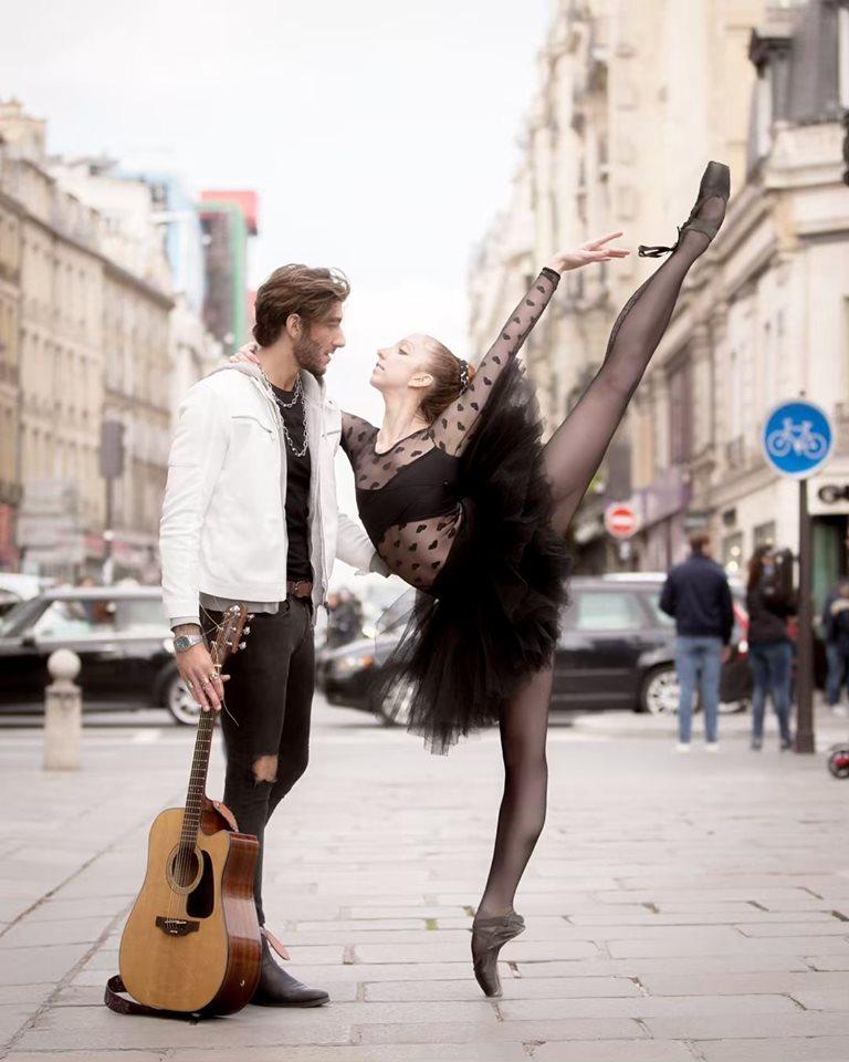 Фото Девушка-балерина стоит перед парнем с гитарой на улице города
