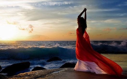 Фото Девушка в красном платье стоит на фоне моря