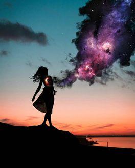 Фото Девушка стоит на фоне неба с исходящим от нее ночного облака