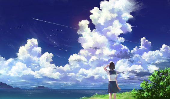 Фото Девушка стоит у моря на фоне огромного облака