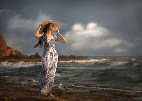 Фото Модель Даша в шляпе и длинном платье стоит на фоне моря. Фотограф Alex