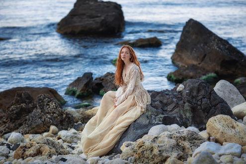 Фото Модель Оксана в длинном платье сидит на камне у моря. Фотограф Бармина Анастасия