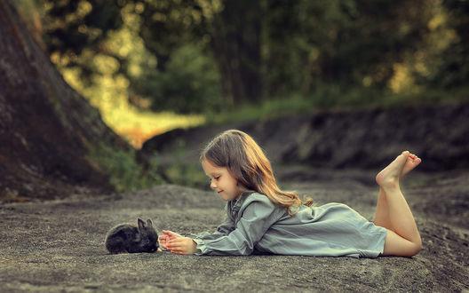 Фото Девочка с кроликом лежат на земле друг напротив друга
