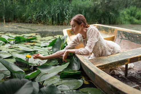 Фото Девушка с лодки протнула руку к водяной лилии. Фотограф Дмитрий Бегма