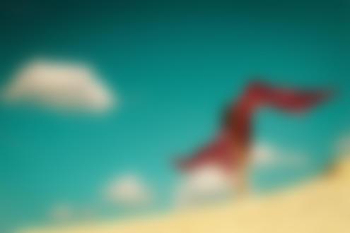 Фото Девушка с красным развевающимся платком стоит на фоне неба. Фотограф Alexei Bazdarev
