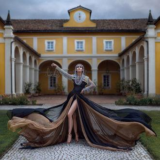 Фото Девушка в длинном платье с весами в руке стоит на фоне дома, by Irina Dzhul