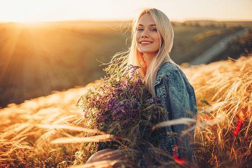 Фото Симпатичная девушка - блондинка с букетом цветов стоит в поле. Фотограф Sergey Shatskov