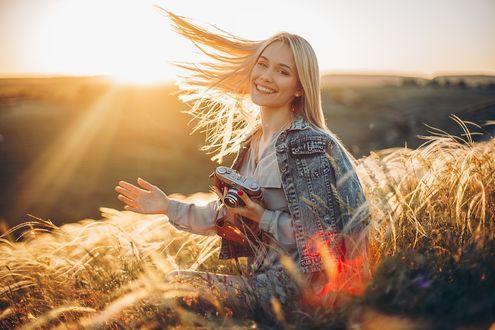 Фото Симпатичная девушка - блондинка с фотоаппаратом стоит в поле. Фотограф Sergey Shatskov