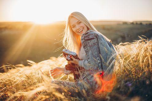 Фото Симпатичная девушка - блондинка с фотоаппаратом в руке стоит в поле. Фотограф Sergey Shatskov