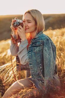 Фото Симпатичная девушка - блондинка с фотоаппаратом в руках сидит на поле. Фотограф Sergey Shatskov