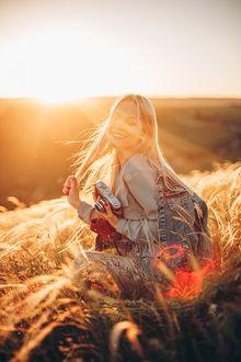 Фото Симпатичная девушка - блондинка с фотоаппаратом сидит на поле. Фотограф Sergey Shatskov