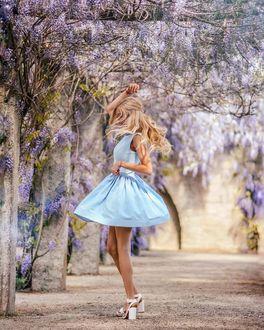 Фото Милая блондинка на улице города с цветущей глицинией, by milena blogs