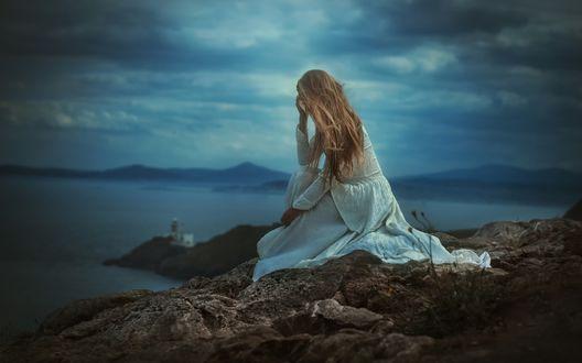 Фото Девушка в белом платье сидит на скале на фоне моря и смотрит вдаль, фотограф TJ Drysdale