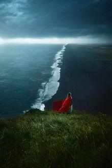 Фото Девушка в красном стоит на вершине на фоне моря, фотограф TJ Drysdale