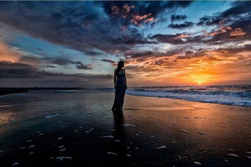 Фото Девушка в длинном платье стоит на фоне моря на закате, by Alma Korreshi