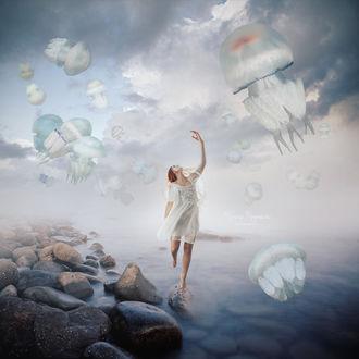 Фото Девушка стоит над водой, приподняв руку к парящим в небе медузам, by Maryna Khomenko