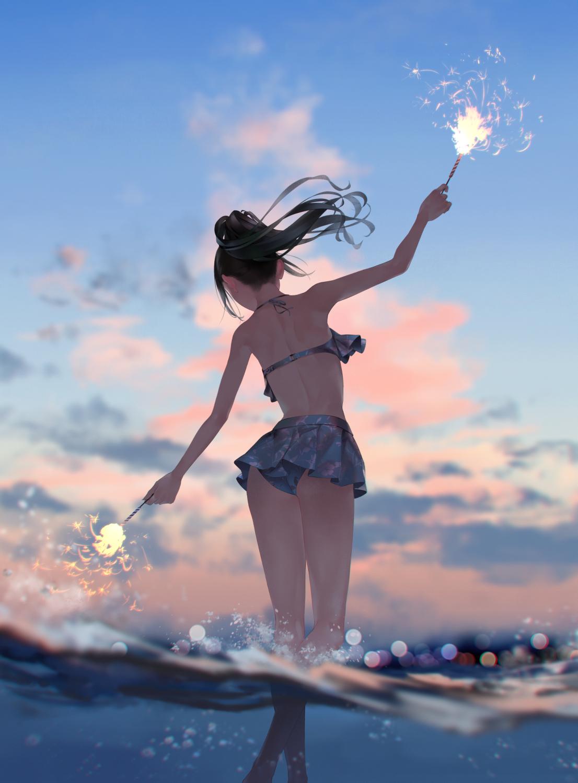Фото Девушка в купальнике с двумя бенгальскими огнями в руках стоит в море