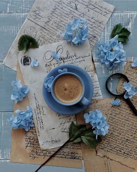 Фото Чашка кофе на блюдце и голубые цветы на столе с письмами