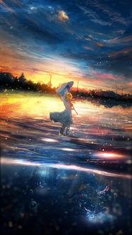 Фото Девочка с подсолнухом в руке стоит в воде на фоне заката