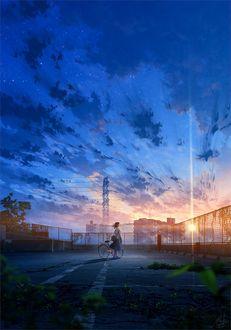 Фото Девочка с велосипедом стоит на фоне домов и облачного неба