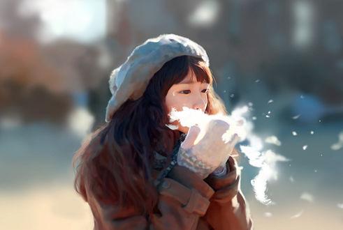Фото Девушка сдувает с ладоней снег